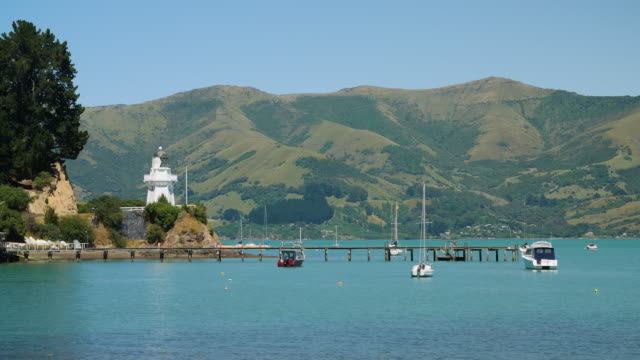 view of akaroa lighthouse and boats in akaroa harbour, new zealand - akaroa stock videos & royalty-free footage