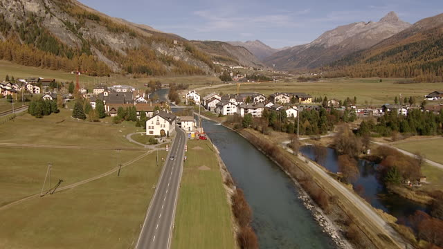 ws aerial view of along inn river crossing village of la punt / la punt, upper engadin, switzerland - inn river stock videos and b-roll footage