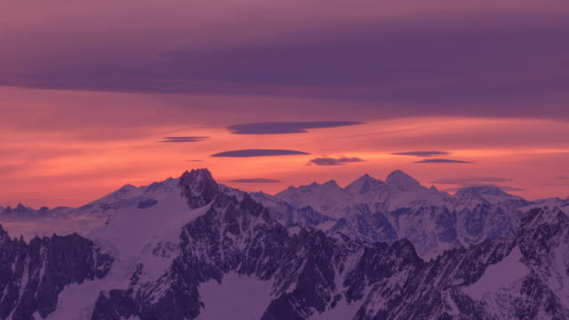 view of alps mountain range under red sky - orange stock videos & royalty-free footage