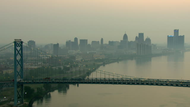 ws aerial view of ambassador bridge to buildings of downtown detroit at sunrise time / detroit, michigan, united states - デトロイト点の映像素材/bロール
