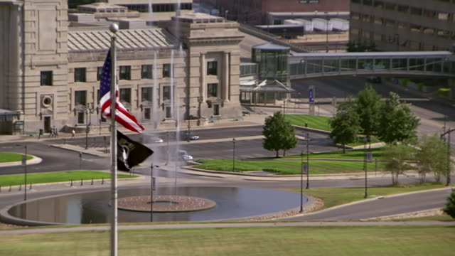 stockvideo's en b-roll-footage met ws view of american and pow mia flags waving with kansas city union station and henry wollman bloch fountain / kansas city, missouri, united states - plaatselijk monument