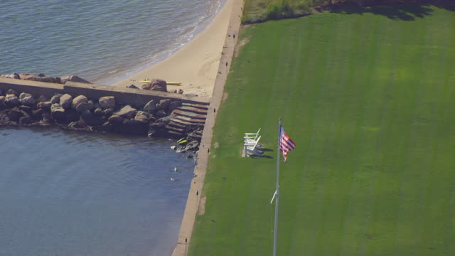ws aerial pov view of american flag at katharine hepburn house/ old saybrook, connecticut, united states - アディロンダックチェア点の映像素材/bロール