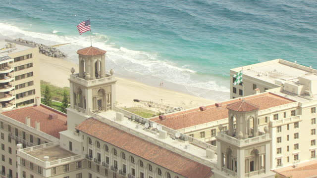 MS AERIAL View of American flag waving at top of Breakers Hotel and front entrance with cars and driveway / Palm Beach, Florida, United States