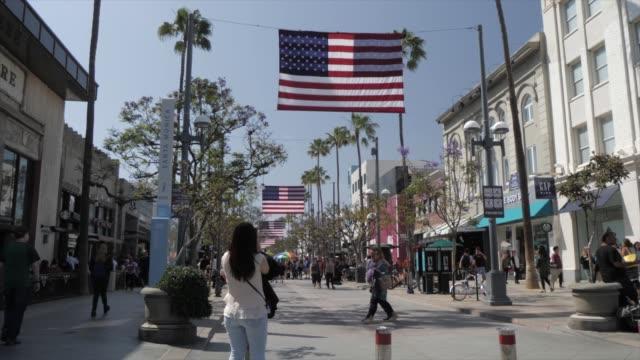 view of american flags on 2nd avenue, santa monica, los angeles, california, united states of america, north america - dolly shot点の映像素材/bロール