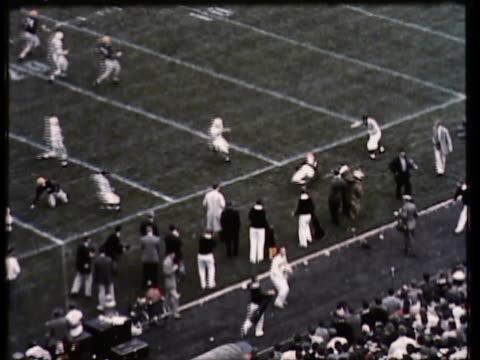 vídeos de stock e filmes b-roll de 1955 ws pan view of american football game, crowd & mascot cheering / usa - 1955