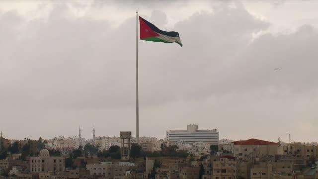 ws ha view of amman with flag of jordan against cloudy sky / jordan - flag stock videos & royalty-free footage