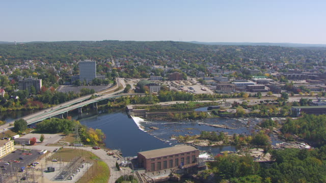 ws aerial pov view of amoskeag mill yard dam with cityscape / manchester, new hampshire, united states - new hampshire stock-videos und b-roll-filmmaterial