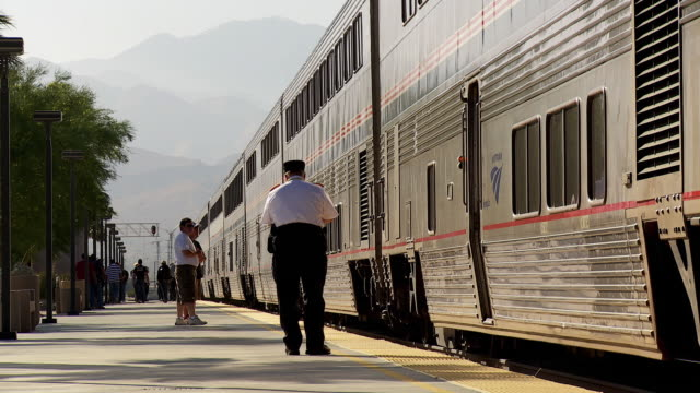 WS View of Amtrak train conductor waiting at platform while passengers boarding train / Palm Springs, California, USA
