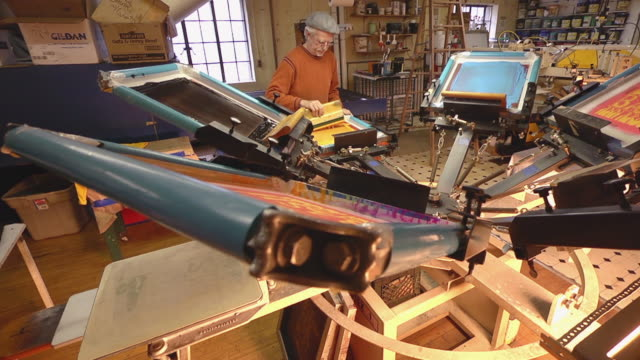 ws view of an artisian pulling ink over a silk screen to print designs on a shirt / ann arbor, michigan, united states - man made stock videos & royalty-free footage