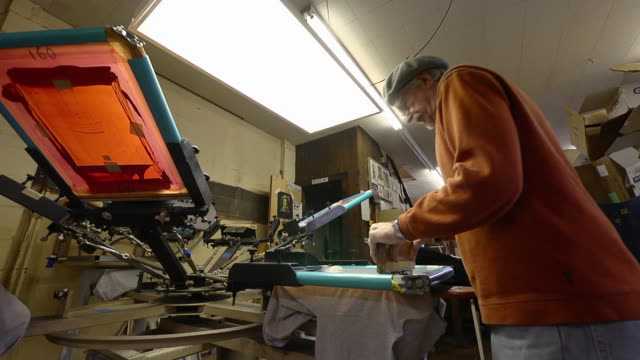 MS LA View of an artisian pulling ink over a silk screen to print designs on a shirt / Ann Arbor, Michigan, United States