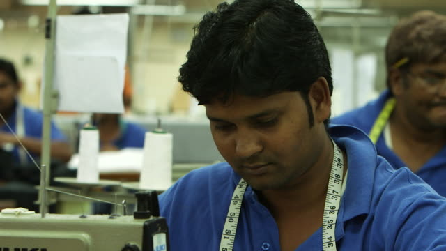 view of an asian tailor with a measuring tape around his neck sitting at his station on a garment factory shop floor. - maßkonfektion stock-videos und b-roll-filmmaterial