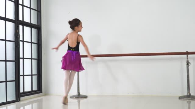 アジアの10代のバレエダンサーが練習し、晴れた日にスタジオクラスでバレエジェスチャーを学び、笑顔で見ます。週末のアクティビティでの毎日の子供のレジャー活動の概念。 - one teenage girl only点の映像素材/bロール