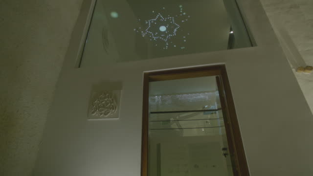 view of an eight pointed star designed to reflect on the ceiling of the bahrain national museum through a play of lights. - octagon stock videos & royalty-free footage