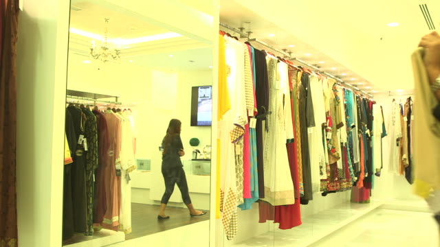 circa 2013 view of an emirati woman as she approaches a mirror in a shop and lifts an embroidered tunic up to see whether it suits her or not - tunic stock videos & royalty-free footage