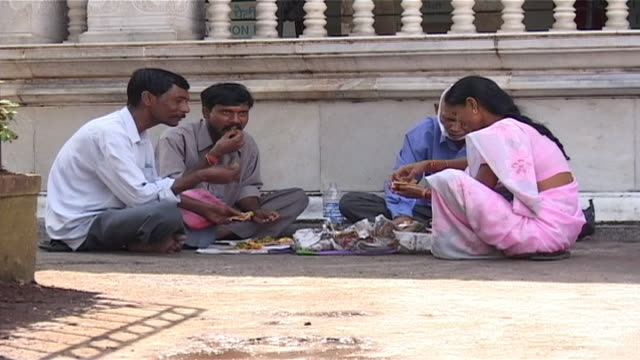 view of an indian family having a picnic in the courtyard of a hindu temple in the city. - indian ethnicity stock videos & royalty-free footage
