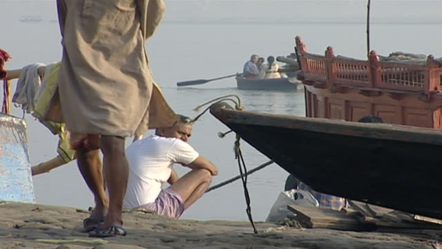 view of an indian man squatting by the river clothes are drying on a pole beside him hindus perform daily ritual ablutions and prayers in the ganges - barefoot stock videos & royalty-free footage