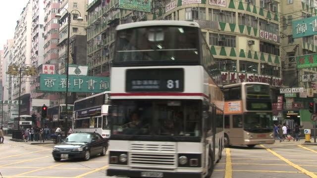 view of an intersection in the city in hong kong china - doppeldeckerbus stock-videos und b-roll-filmmaterial