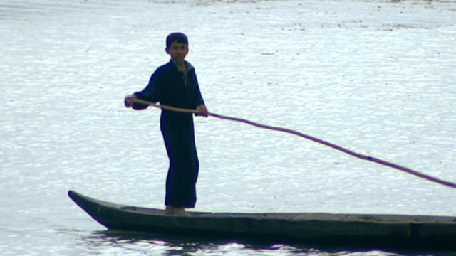 view of an iraqi boy paddling his canoe with a pole on the shatt al arab river. shatt al arab is a river formed by the confluence of tigris and... - basra video stock e b–roll