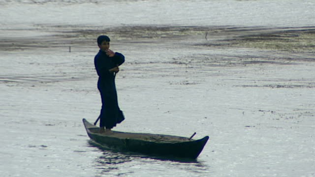 view of an iraqi boy paddling his canoe with a pole on the shatt al arab river. shatt al arab is a river formed by the confluence of tigris and... - ペルシャ湾点の映像素材/bロール