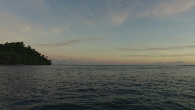 view of an island from the sea at the end of the day - huahine island stock videos and b-roll footage