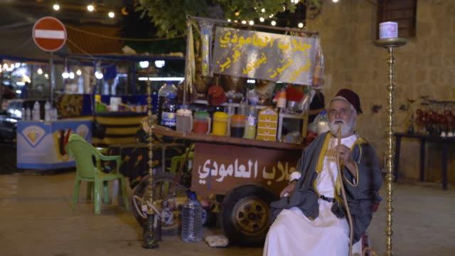 view of an old lebanese man smoking an argileh wearing an abaya and tarboosh sitting in front of his jallab kiosk in tripoli's medieval souk - door to door salesperson stock videos & royalty-free footage