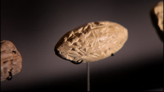 view of an olive shaped clay tablet or seal impressed with ancient cuneiform writing, at the bahrain national museum. - 足根点の映像素材/bロール