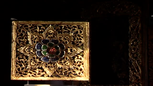 vídeos de stock e filmes b-roll de view of an ornately carved and intricately bejeweled wooden screen with a central flower motif. - trabalho de metal