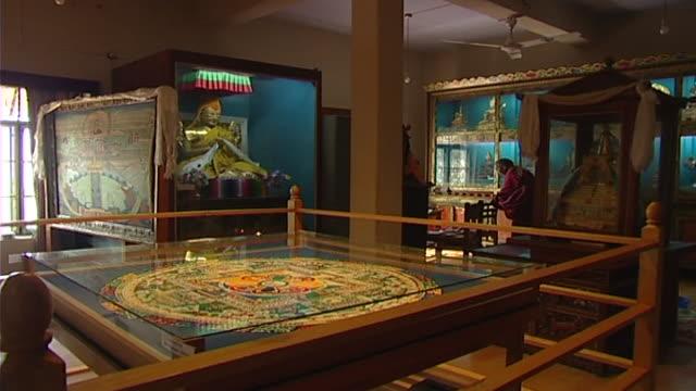 view of an ornately embroidered mandala situated beneath a glass viewing pane. - skåp med glasdörrar bildbanksvideor och videomaterial från bakom kulisserna