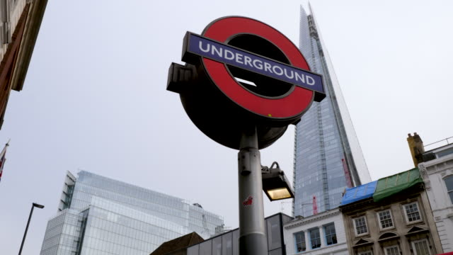 View of an underground sign and The Shard towering above buildings on a grey day in London