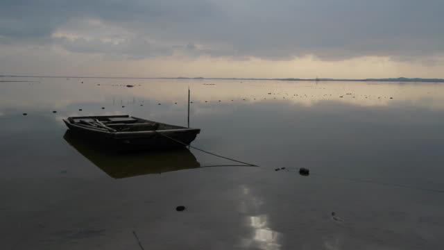 stockvideo's en b-roll-footage met view of anchoring boat on the water - voor anker gaan