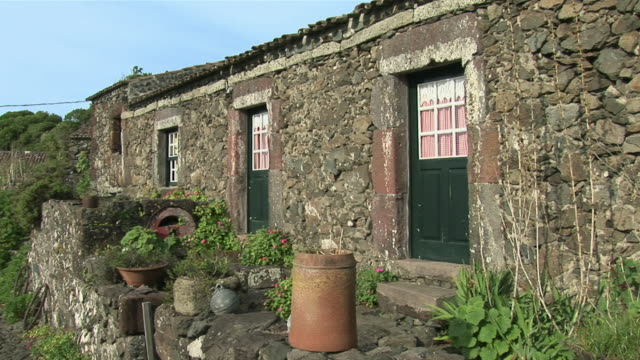 ws pan view of ancient farm village, now hotel / faja grande, flores island, azores, portugal - アゾレス諸島点の映像素材/bロール