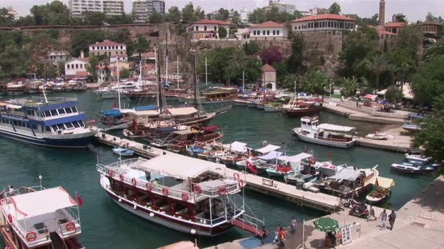 ms pan view of ancient harbour and city with fishing boats and excursion ships / antalya, turkish riviera, turkey - komplett stock-videos und b-roll-filmmaterial