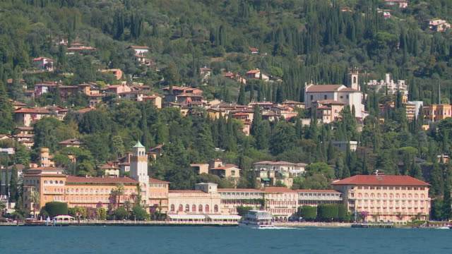 WS View of ancient luxury hotels on edge of lake and village climbing up hill / Gardone Riviera, Brescia, Italy