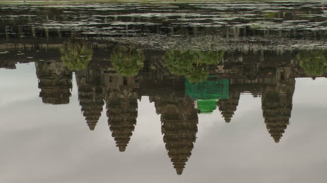 ms tu view of angkor wat temple reflection in moat to actual temple with clouds and green scaffolding / siem reap, siem reap province, cambodia - moat stock videos & royalty-free footage
