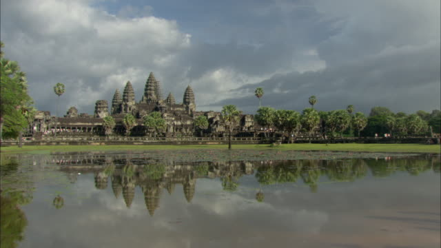 ws zi view of angkor wat temple with lake in foreground / angkor, cambodia - cambodian culture stock videos and b-roll footage