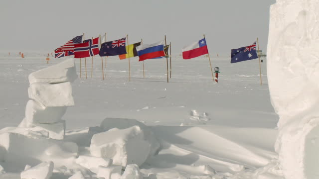 vidéos et rushes de ws view of antarctic treaty state flags at ceremonial south pole and ice blocks / south pole, antarctica - antarctique