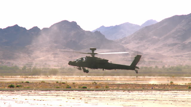 ws pan ts view of apache military attack helicopter taking off on remote desert airfield / los angeles, california, usa - アパッチヘリコプター点の映像素材/bロール