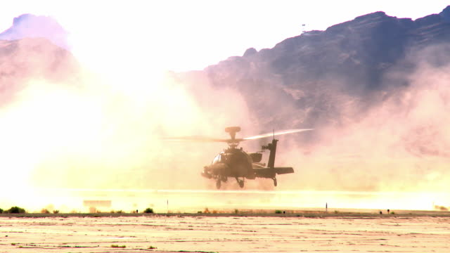 ws zi zo view of apache military attack helicopter with remote desert airfield slowly lifting off sand and dust / los angeles, california, usa - アパッチヘリコプター点の映像素材/bロール