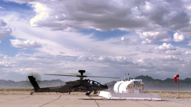 ws view of apache military attack helicopter with rotors spinning and parked near fuel storage tanks desert / los angeles, california, usa - attack helicopter stock videos and b-roll footage
