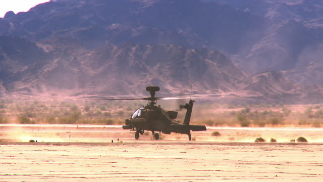 ws pan view of apache military attack helicopter with rotors spinning, taking off on dusty desert / los angeles, california, usa - apache helicopter stock videos and b-roll footage