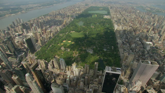 ws aerial view of approaching central park with buildings surrounding park in manhattan / new york, united states - central park manhattan stock videos and b-roll footage