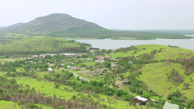vídeos de stock e filmes b-roll de ws aerial view of approaching wichita mountains with building by water and water dam / oklahoma, united states - wichita
