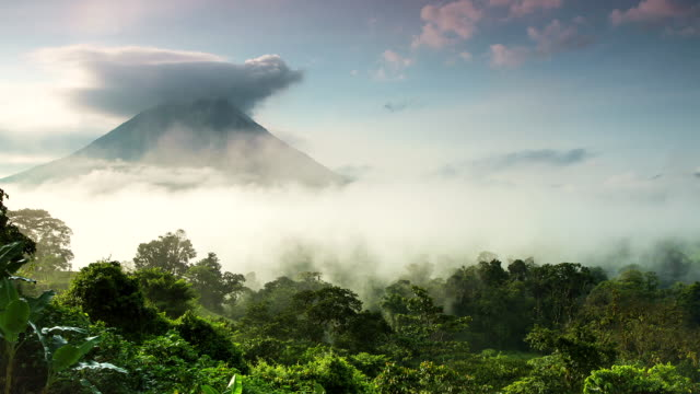 ws t/l view of arenal volcano and jungle in morning mist with clouds moving / la fortuna, alajuela, costa rica - costa rica video stock e b–roll