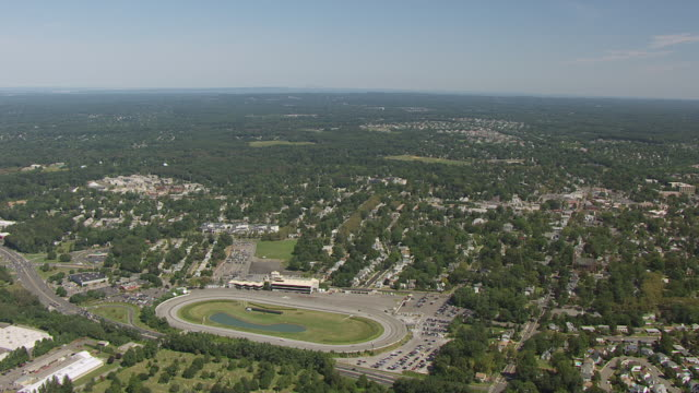 ws aerial view of around freehold raceway with racers on track / freehold borough, new jersey, united states - pferderennbahn stock-videos und b-roll-filmmaterial