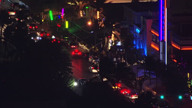 ms aerial view of art deco hotels and buildings at night and cars driving down ocean drive in south beach at night / miami, florida, united states - アールデコ地区点の映像素材/bロール