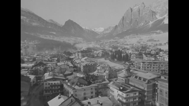 view of ascending gondola lift from descending gondola traveling on snowy mountainside / aerial italian village of cortina and snow covered mountain... - bobsleighing stock videos & royalty-free footage
