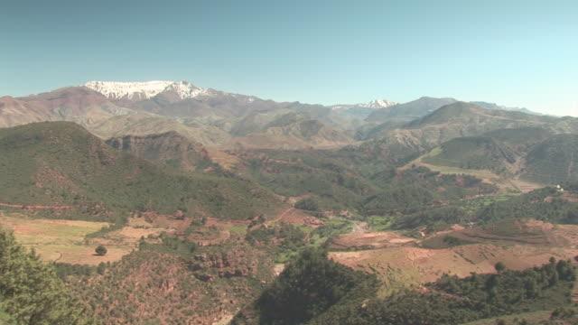 vídeos de stock e filmes b-roll de ws pan view of atlas mountain range with green valley / near marrakech, marrakech, morocco  - paisagem cena não urbana