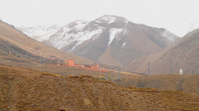 ws view of atlas mountains with small buildings / marrakech, tensift, morocco  - wiese点の映像素材/bロール