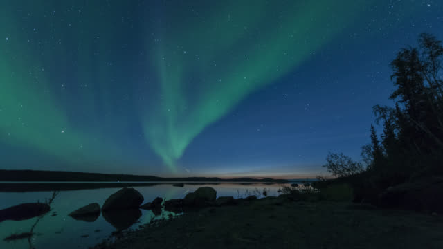 ws t/l view of aurora during early summer over calm lake with reflection / yellowknife, northwest territories, canada  - オーロラ点の映像素材/bロール