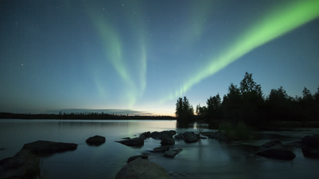 WS T/L View of aurora during early summer with rocks in foreground and reflection on calm water / Yellowknife, Northwest Territories, Canada